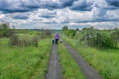 La mujer y los niños caminan en el camino debajo de las nubes oscuras fotografía de archivo libre de regalías