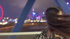 La mujer y una muchacha está caminando en un puente elevado en la rueda de Victoria Harbor Ferris almacen de video