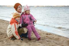 La mummia con i bambini si siede sulla banca di fiume fotografia stock