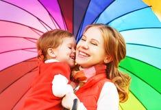 La mummia della famiglia e la figlia felici del bambino con l'arcobaleno hanno colorato il umbrell Immagine Stock