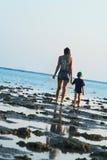 La mummia ed il figlio camminano su un litorale Fotografie Stock