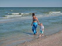 La mummia ed il figlio stanno camminando lungo la spiaggia La giovane madre con il ragazzino del bambino è sulla spiaggia Famigli Immagini Stock
