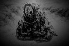 La mummia scura si siede sulle rovine nella neve fotografia stock libera da diritti