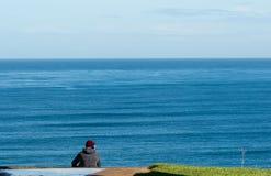 La musica d'ascolto del giovane sta sedendosi sul bordo della scogliera del mare Con un fondo del cielo blu in un giorno di molla immagini stock