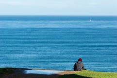 La musica d'ascolto del giovane sta sedendosi sul bordo della scogliera del mare fotografia stock libera da diritti