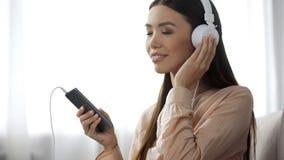 La musique de écoute de belle dame dans des écouteurs, aime la station de radio, plaisir photo libre de droits