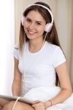 La musique de écoute de femme dans le lit avec les écouteurs roses après se réveillent, écrivant un jour heureux et décontracté a Photographie stock