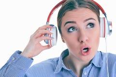 La musique de écoute de femme avec des écouteurs d'un téléphone intelligent et demande ce qui ? Photographie stock libre de droits