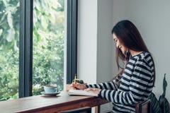 La musique de écoute de femme de livre asiatique d'écriture avec la séance mobile au restaurant de café près de la fenêtre voient image libre de droits