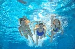La nadada de la familia en la piscina o mar subacuático, la madre y los niños se divierten en agua Imágenes de archivo libres de regalías