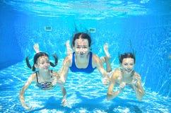 La nadada de la familia en madre de la piscina y niños activos subacuáticos, felices se divierte en agua, deporte de los niños Foto de archivo