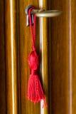 La nappa rossa legata intorno ad ottone digita il buco della serratura della porta Immagini Stock