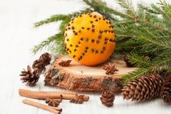 La naranja adornada con canela de palillos de los clavos y el abeto ramifican Imagen de archivo