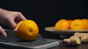 La naranja cutted por el cuchillo afilado en el tablero de la roca, las rebanadas de naranja fresca, la fruta y las vitaminas, di almacen de metraje de vídeo