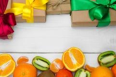 La naranja de la fruta, la mandarina y la caja de regalo con la cinta arquean en el fondo retro de madera blanco foto de archivo