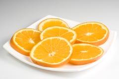 La naranja del corte en una placa Fotos de archivo libres de regalías