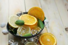 La naranja del limón deja la fruta cítrica de las cáscaras del mar del hielo del cubo en un cuenco negro Fotos de archivo libres de regalías