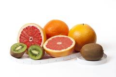 La naranja, el pomelo, el kiwi y el tipe miden en pulgadas sobre blanco Fotografía de archivo libre de regalías