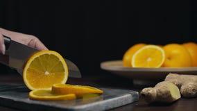 La naranja es cortada por el cuchillo afilado en el tablero de la roca, las rebanadas de naranja fresca, la fruta y las vitaminas almacen de video