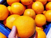 La naranja está en una mano Mucho más están detrás de las escenas en una cesta azul fotos de archivo libres de regalías