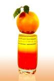 La naranja está sobre el vidrio con el jugo Fotos de archivo libres de regalías