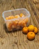 La naranja fresca adentro guarda la caja plástica en el fondo de madera Foto de archivo