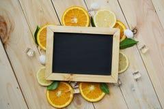 La naranja negra del tablero sale del modelo de la fruta cítrica de las cáscaras del mar del hielo del cubo encendido Fotografía de archivo