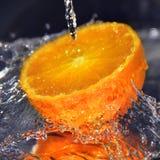La naranja y el agua de Jucy salpica el foco selectivo Imagen de archivo libre de regalías