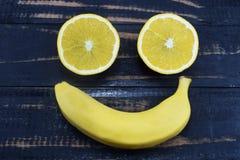 La naranja y el plátano mienten en la tabla bajo la forma de sonrisa Imágenes de archivo libres de regalías