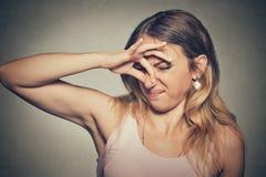 La nariz de los pellizcos de la mujer con miradas de los fingeres con repugnancia algo apesta el mún olor imágenes de archivo libres de regalías