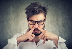 La nariz de los pellizcos del hombre con miradas de los fingeres con repugnancia algo apesta el mún olor imagen de archivo libre de regalías