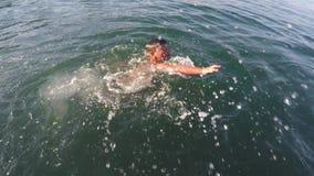 La natación alegre del muchacho en el mar y se divierte almacen de metraje de vídeo