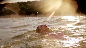 La natación de la mujer joven en el mar en ella detrás durante la puesta del sol que hace el agua salpica en la cámara lenta revé