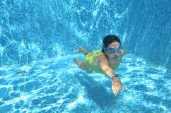 La natación del nadador de la chica joven debajo del agua en piscina y tiene la diversión, el adolescente que se zambulle bajo el Fotografía de archivo libre de regalías
