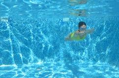 La natación del nadador de la chica joven debajo del agua en piscina y tiene la diversión, el adolescente que se zambulle bajo el Foto de archivo libre de regalías