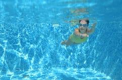 La natación del nadador de la chica joven debajo del agua en piscina y tiene la diversión, el adolescente que se zambulle bajo el Imagen de archivo libre de regalías