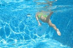 La natación del nadador de la chica joven debajo del agua en piscina y tiene la diversión, el adolescente que se zambulle bajo el Foto de archivo