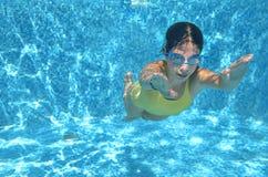 La natación del nadador de la chica joven debajo del agua en piscina y tiene la diversión, el adolescente que se zambulle bajo el Fotos de archivo libres de regalías