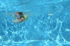 La natación del nadador de la chica joven debajo del agua en piscina y tiene la diversión, el adolescente que se zambulle bajo el Imagenes de archivo