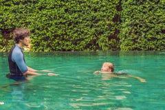 La natación masculina del instructor para los niños enseña a un muchacho feliz a nadar en la piscina imagenes de archivo