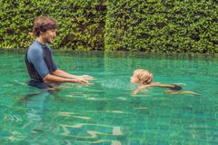 La natación masculina del instructor para los niños enseña a un muchacho feliz a nadar en la piscina fotos de archivo