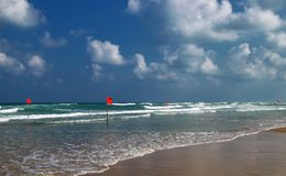La natation est dangereuse dans des vagues de mer Battement d'avertissement rouge de drapeau dans le vent au temps orageux images libres de droits