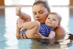 La natation heureuse de mère avec la fille adorable mignonne de bébé dans la station thermale de dépense de piscine vacations Photographie stock