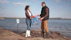 La natura ambientale, attivisti dei volontari di paia pulisce lungomare inquinante del fiume da rifiuti di plastica e raccolto de stock footage