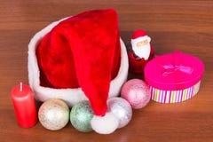 La natura morta del nuovo anno, candela, giocattoli, cappuccio del regalo e padre Frost fotografia stock