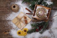La natura morta del nuovo anno con le ore, la neve ed i rami dell'pelliccia-albero Immagini Stock Libere da Diritti
