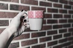 La natura morta della cucina, mano femminile con il bello manicure giudica una tazza di bianco rosa isolata su un fondo di vecchi fotografia stock libera da diritti
