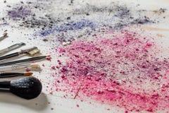 La natura morta di Girlie con le spazzole di trucco, arrossisce ed i colori dell'ombretto Fotografia Stock