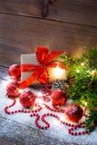 La natura morta di Natale con i giocattoli del contenitore di regalo e del ramo e di festa di albero dell'abete infiamma luci del immagini stock