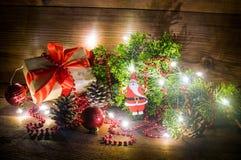 La natura morta di Natale con i giocattoli del contenitore di regalo e del ramo e di festa di albero dell'abete infiamma luci del fotografie stock